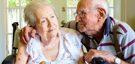 Elderly eighty plus year old woman in a wheel chair in a home setting with her husband.