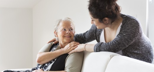 young caregiver supporting senior woman, sitting on sofa, putting her hnds on her shoulder, smiling