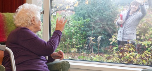 An independent living elderly client waving goodbye to her professional carer through the window of her property